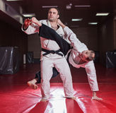 Two karate fighters showing technical skill while practicing Royalty Free Stock Image