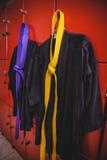 Two karate uniforms hanging on locker Stock Image