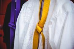 Two karate uniforms hanging on locker Stock Photography