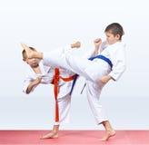 Two karateka beat kicks on the red mats Royalty Free Stock Images