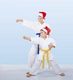 Two karateka in caps of Santa Claus beat punch arm Stock Photos