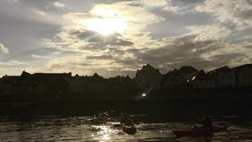 Two kayak floating in slow motion. Action at sunset in the city landscape stock footage