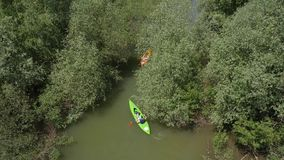 Two kayakers paddling down the river stock footage
