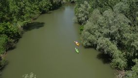 Two kayakers paddling down the river stock video footage