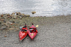 Two Kayaks. Two red kayaks on the beach in front of the water stock images