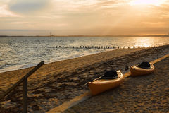 Two Kayaks on the beach at Sunset in Cape Cod. Two kayaks waiting on the beach under a brilliant sunset in Truro, Cape Cod Massachussets Stock Photos