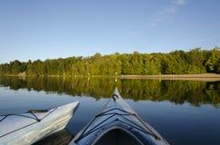 Two Kayaks on Charleston Lake. Two kayaks floating on calm Charleston Lake facing the beach with the evening light Royalty Free Stock Photography