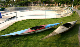 Two kayaks on grass. With drained lake or pond in background Royalty Free Stock Photography