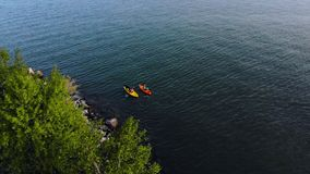 Two kayaks moving on the sea top view. Dog in boat. Sports kayak, canoe in the lake on calm water in autumn day stock footage