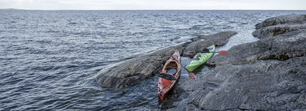 Two kayaks parked on the rocky shore of the lake. Panorama. Stock Photography