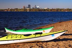 Urban Kayaking. Two kayaks rest on the shores of Lake Calhoun, with the Minneapolis skyline inthe background stock photography