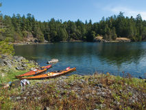 Two kayaks on rocky shore. Two wood strip kayaks on rocky shore of the clear water Smuggler's Cove on the Sunshine Coast of British Columbia, Canada Stock Photo
