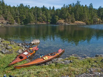 Two kayaks on rocky shore. Two wood strip kayaks on rocky shore of the clear water Smuggler's Cove on the Sunshine Coast of British Columbia, Canada Royalty Free Stock Images