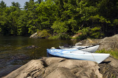 Kayaks on the Rocky Shoreline Royalty Free Stock Photos