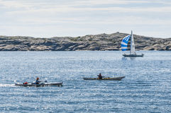Two kayaks and a sailingboat Swedish West Coast Stock Image