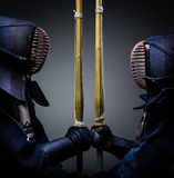Two kendo fighters opposite each other with shinai. Two kendo fighters opposite each other with bokuto. Japanese martial art of sword fighting Royalty Free Stock Images