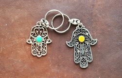 Two key rings in the form of Fatima Hand on a brown leather background. Ancient symbol and traditional modern tourist souvenir of stock images