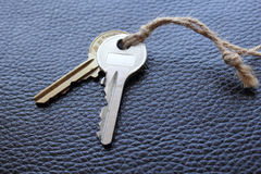 Two keys tied with string on black leather Royalty Free Stock Images