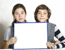 Two kid boy and girl hold blank paper sheet Royalty Free Stock Photography
