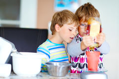 Two kid boys baking cake in domestic kitchen Stock Images