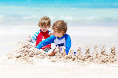 Two kid boys building sand castle on tropical beach of Bora Bora Royalty Free Stock Photography