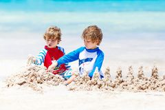 Two kid boys building sand castle on tropical beach of Boracay, Philippines stock photo