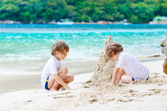 Two kid boys building sand castle on tropical beach Stock Photo