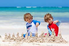 Two kid boys building sand castle on tropical beach Stock Image