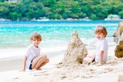 Two kid boys building sand castle on tropical beach Stock Photos