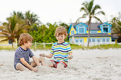Two kid boys building sand castle on tropical beach Stock Image