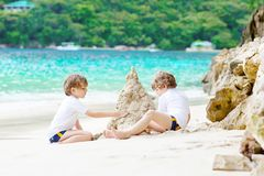 Two kid boys building sand castle on tropical beach. Two little kids boys having fun with building a sand castle on tropical beach of Seychelles. children stock image
