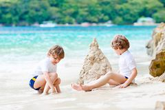Two kid boys building sand castle on tropical beach. Two little kids boys having fun with building a sand castle on tropical beach of Seychelles. children stock photos