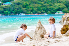 Two kid boys building sand castle on tropical beach Royalty Free Stock Image