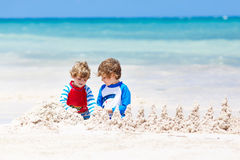 Two kid boys building sand castle on tropical beach of Playa del Carmen, Mexico. Two little kids boys having fun with building a sand castle on tropical beach of Royalty Free Stock Photos