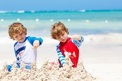 Two kid boys building sand castle on tropical beach of Playa del Carmen, Mexico. Two little kids boys having fun with building a sand castle on tropical beach of royalty free stock photography
