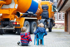 Two kid boys and concrete mixer near house Royalty Free Stock Image
