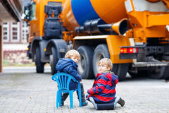 Two kid boys and concrete mixer near house Stock Photography