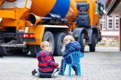 Two kid boys and concrete mixer near house Royalty Free Stock Photos
