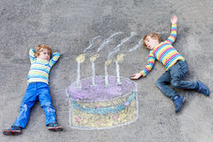 Two kid boys having fun with colorful birthday cake drawing with Royalty Free Stock Photography