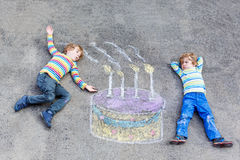 Two kid boys having fun with colorful birthday cake drawing with Stock Photography