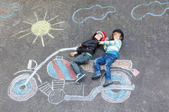 Two kid boys in helmet with motorcycle picture drawing with colo Stock Image