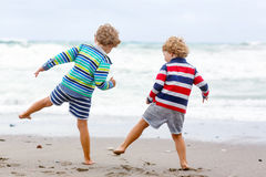 Two kid boys playing on beach on stormy day Stock Image