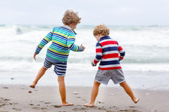 Two kid boys playing on beach on stormy day Royalty Free Stock Photo