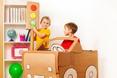 Two kid boys playing drivers with handmade car. 5 years old boy pointing to the green light of handmade traffic lights while his friend driving toy cardboard car Royalty Free Stock Photo