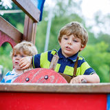 Two kid boys pretends driving an imaginary car on playground, Stock Image