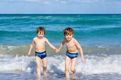 Two kid boys running on ocean beach in Florida Royalty Free Stock Photo