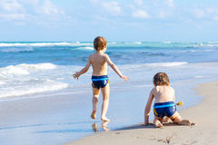 Two kid boys running on ocean beach in Florida royalty free stock images