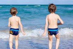 Two kid boys running on ocean beach. Little children having fun Stock Images
