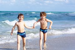 Two kid boys running on ocean beach. Little children having fun Stock Photos