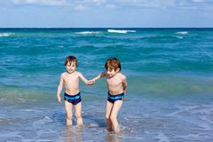 Two kid boys running on ocean beach. Little children having fun. Two happy little kids boys running on the beach of ocean. Funny cute children, siblings, twins royalty free stock photo